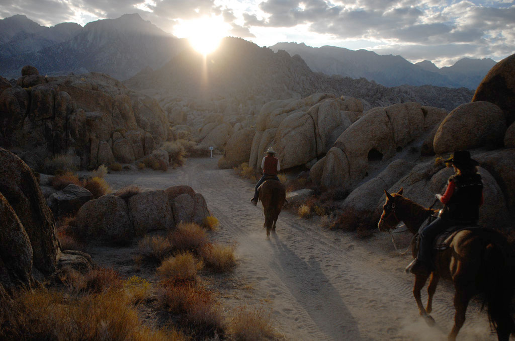 Two Riders riding on a trail through rocks into the sunset.